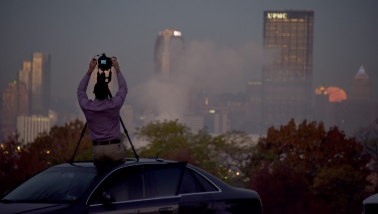 Jason Furda, of Bridgeville, takes photos from the sunroof of his car, during the setting of the supermoon between the Koppers Building and the Gulf Tower. Jason was taking photos in Schenley Park early Monday morning Nov. 14, 2016. (Darrell Sapp/Post-Gazette)