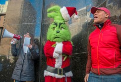 """Abby Cartus, left, a graduate student at the University of Pittsburgh and Douglas Ward, a United Steel worker, chant slogans outside Senator Pat Toomey's office while the """"Grinch"""" listens on Wednesday, December 06, 2017 Downtown. Members of the USW Graduate Student Organizing Committee and their fellow University of Pittsburgh students delivered letters to Senator Pat Toomey, urging him to keep anti-education provisions passed by the House of Representatives out of the final version of the tax bill. (Lake Fong/Post-Gazette)"""
