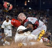 Pirates Starling Marte slides into home plate against Reds Tucker Barnhart in the sixth inning Wednesday, August 2, 2017 at PNC Park in Pittsburgh. (Matt Freed/Post-Gazette)