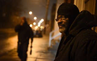 A few blocks from his McKees Rocks home, Steve Kelley waits for a bus that will take him to his night job at Gateway Center in Downtown Pittsburgh on Wednesday, Feb. 8, 2017. (Steve Mellon/Post-Gazette)