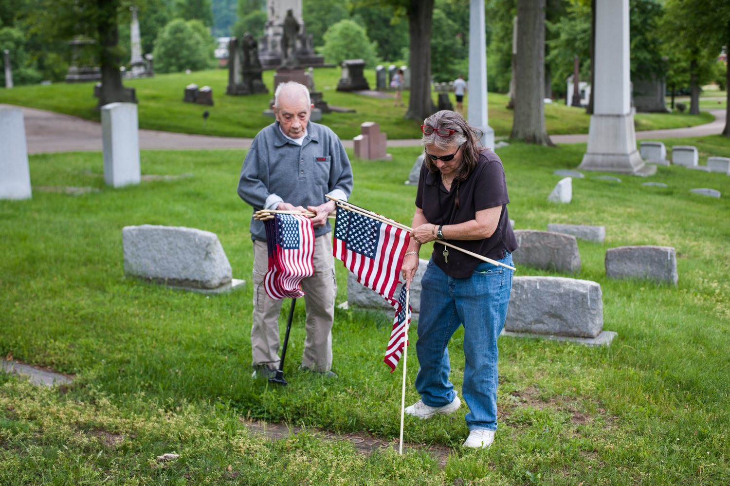 "Event organizers Marlene Scholze, right, 58, and World War II veteran Pietro Fantone, 94, both of Bloomfield, volunteer to place American flags at the graves of veterans on Monday, May 21, 2018, in preparation for Memorial Day at Allegheny Cemetery in Lawrenceville. ""I have tears in my eyes every time I come here,"" said Fantone, who has been coming to volunteer to place flags at the graves of veterans for 69 years. (Stephanie Strasburg/Post-Gazette)"