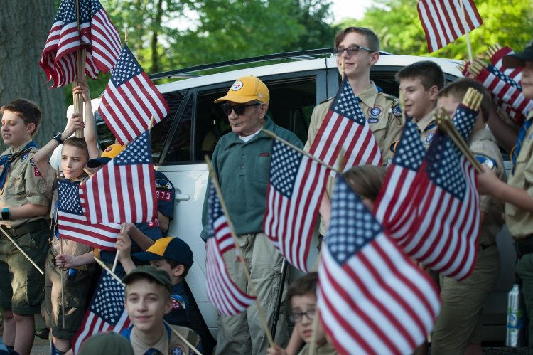 Pietro Fantone, a World War II veteran, poses with Boy Scouts from Troop and Pack 373 in Shadyside, as the troop places flags on the gravesite of veterans in advance of Memorial Day, on Wednesday, May 23, 2018, at the Allegheny Cemetery in Lawrenceville. Fontana has been placing flags at the cemetery for 68 years. (Rebecca Droke/Post-Gazette)