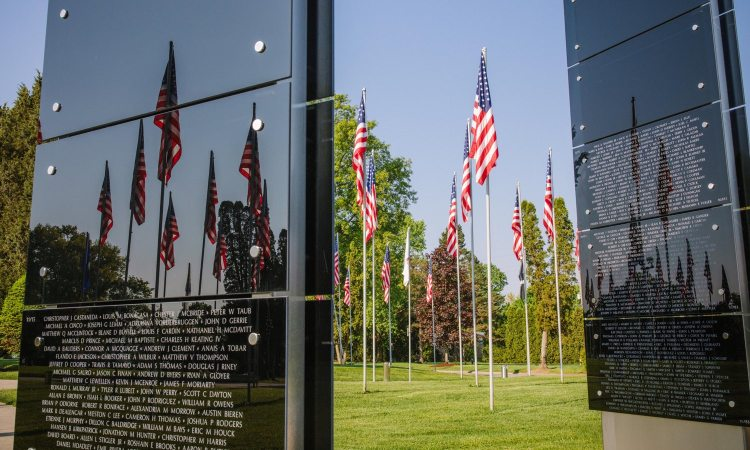 The Avenue of 444 Flags at Hillcrest Memorial Park cemetery reflects in the War on Terror Memorial on Thursday, May 24, 2018, in Hermitage. The flags were raised during the Iran hostage crisis and mark the 444 days of captivity. The War on Terror Memorial lists the names of more than 7,000 servicemen and women who have died in the war on terror. (Andrew Rush/Post-Gazette)