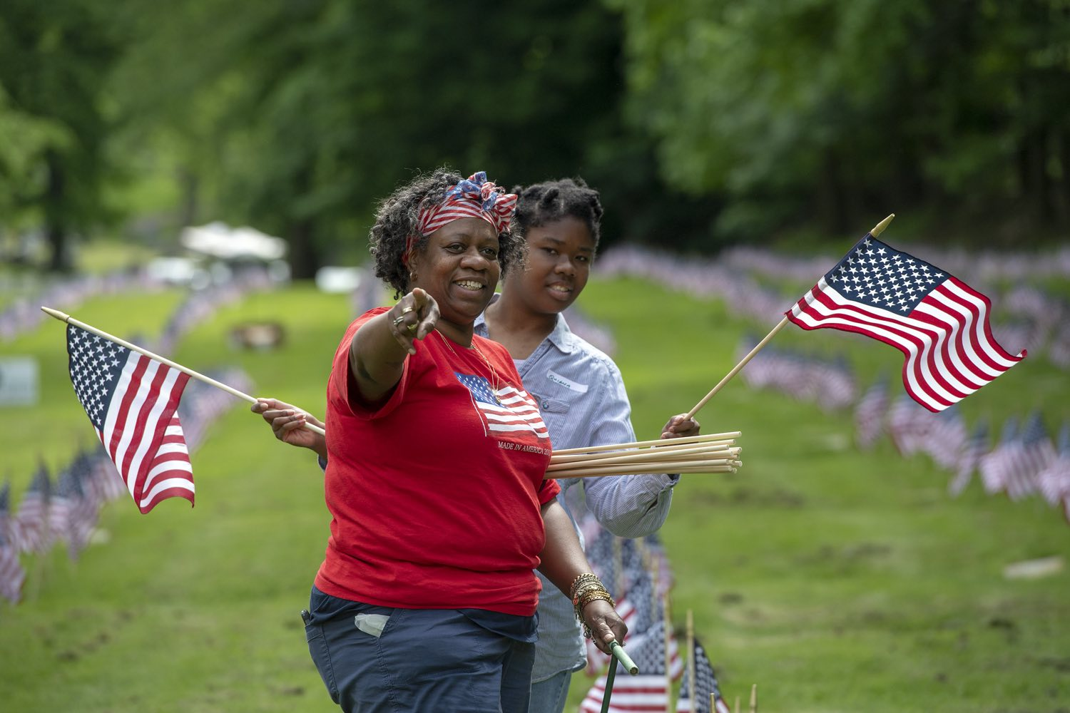Day program counselor Rachelle Coburn points toward geese to show Quiana Reeves, 24, of the North Side, as the two place flags on the graves of military veterans with Pittsburgh Mercy Intellectual Disabilities Services on Wednesday, May 22, 2018, at Allegheny Cemetery in Lawrenceville. (Steph Chambers/Post-Gazette)