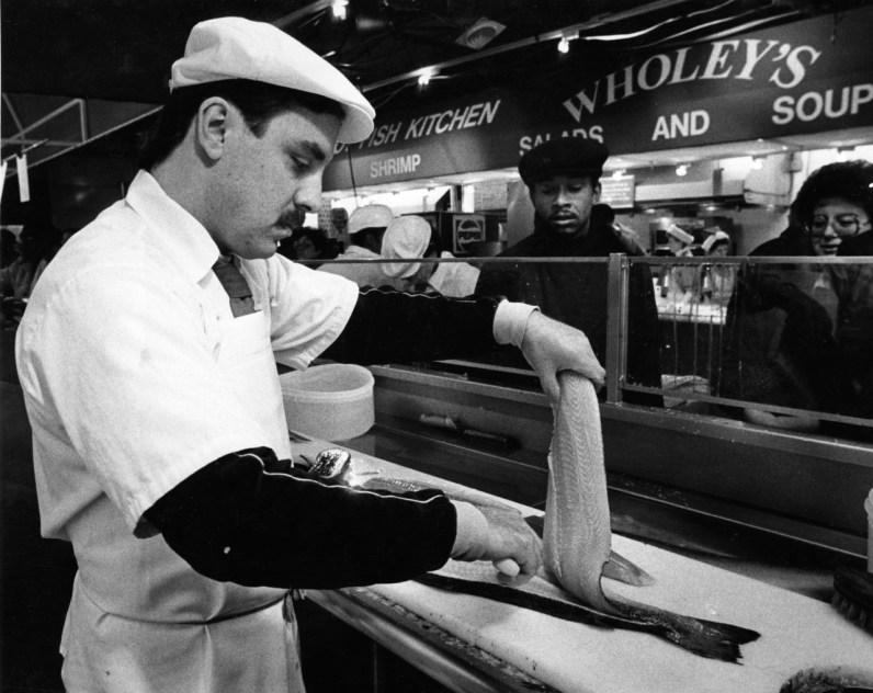 Mike Hartman cuts Norwegian salmon at Wholeys fish market in the Strip, December 1986. (John Beale/Post-Gazette)