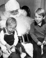 Timmy Betler, 3, fights to keep his Christmas spirit in light of the competition from his 18-month old brother, Michael. (James Klingensmith/Post-Gazette, 1982)