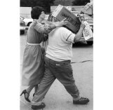 Gill, with box on head, was escorted from court by attorney Shelly Friedman in 1979. (Harry Coughanour/Post-Gazette)
