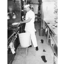 Cook John Gibbons works on broken floor tiles at Frank & Wallys on Forbes Avenue in 1971. (Pittsburgh Press photo)