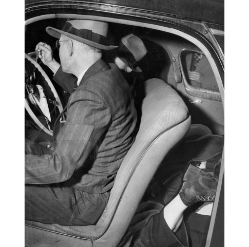 Detectives brush the death car for fingerprints while Garrow lies jammed awkwardly in the back floorboard. (Pittsburgh Press photo)