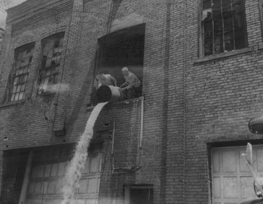 May 22, 1958: Authorities dump a barrel out the window of an abandoned building used as a moonshine distillery. (Pittsburgh Post-Gazette)