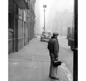 A man waits in solitude for a trolley on a city street. (Pittsburgh Press photo)