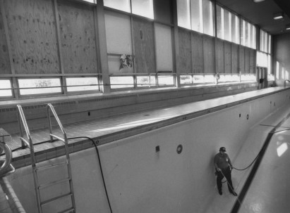 Sept. 24, 1990: Dick Garrity, a Woodland Hills School District worker, cleans glass out of the pool after vandals broke windows in the school — $40,000 in repairs. (John Heller/The Pittsburgh Press)