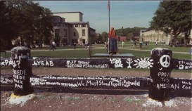 CMU prepares for its peace rally at the Fence, which was painted with messages at a vigil held the night of the tragedy on Sept. 11, 2001. (Photo by Eileen Shiue)