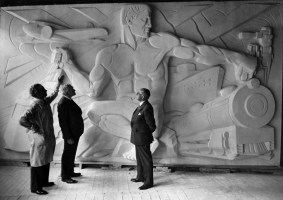 Sculptor Frank Vittor, left, displays a clay model of one of the panels to be carved in granite on the entrance pylons. (Westinghouse Electric and Manufacturing Co.)