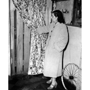 Theresa Weichel shows one of two boarded-up doors in the house. (Pittsburgh Press photo)