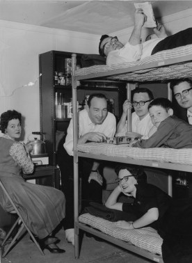 "March 18, 1960: The seven people who spent last weekend in a simulated fallout shelter at American Institute of Research, 410 Amberson Avenue, Shadyside. On the top bunk, Robert Smith, reading. Nancy Newton is at the ""kitchen"" stove at left. Second bunk: Frank McKenna, Gil Dannels, Tommy McKenna, 8, and James Altman. In lower bunk is Sara Bryson. (Bill Levis/Pittsburgh Sun-Telegraph)"