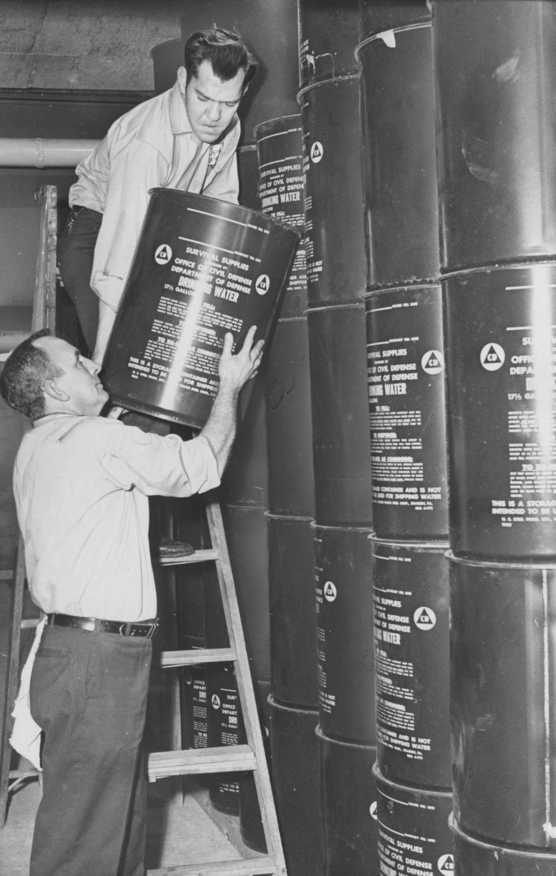 Feb. 5, 1970: Two employees of Duquesne University's housekeeping department, Milton Geisler, left, and James Apostal, lift a 17 1/2 gallon can of water into place in the fallout shelter beneath the school's student union building. (Anthony Kaminski/The Pittsburgh Press)
