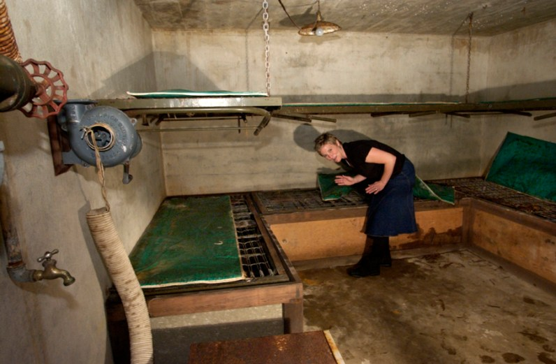 Renee MacDougall inside the eight-person bomb shelter her family found buried behind their recently-purchased Edgeworth home. Containers of food and water are still in storage beneath of the lower rack of bunk beds. A hand-crank ventilator is mounted on the wall at left. Photo made Monday, May 13, 2002. (Bob Donaldson/Post-Gazette)