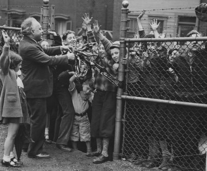 A crowd of Hill District youngsters waits impatiently as Sidney Teller, director of the Irene Kaufmann Settlement, cuts the ribbon on a playground filled with slides and swings. The May 1937 image is from The Pittsburgh Press