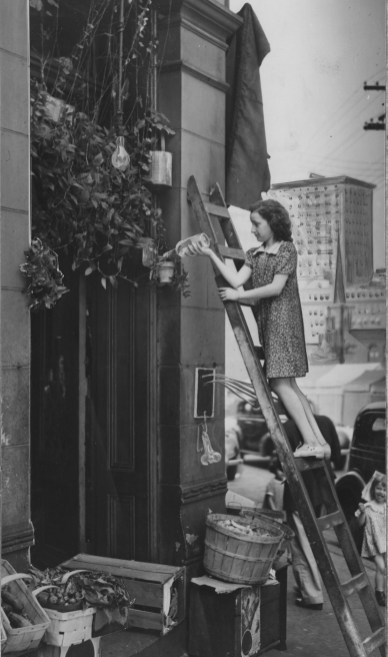 In this 1938 picture, Dolores Antonacci tends flowers outside the Irene Kaufmann Settlement, just blocks from the city's skyscrapers.