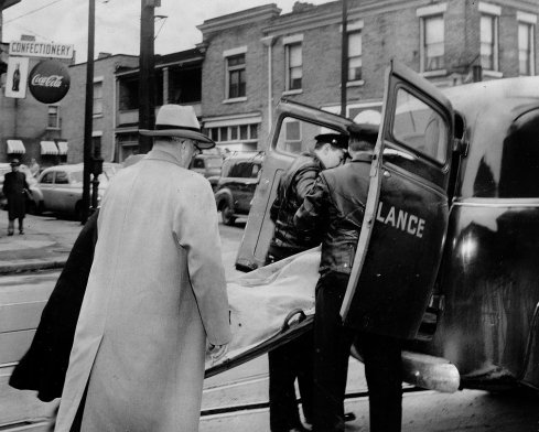 Walter Henry's body is removed from the scene. (Pittsburgh Press)