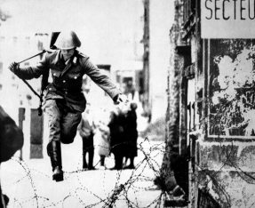 An East Berlin soldier defects by leaping over coils of barbed wire in 1961. (Associated Press)