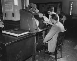 May 27, 1957: A librarian assists another employee at The Pittsburgh Press with a microfilm machine.