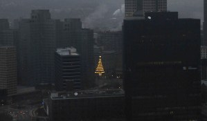 As the skys began to lighten on a foggy Christmas morning, December 25, 2012, the view from Mt. Washington had one bright spot, the Unity Tree on the old Horne's department store building. (Larry Roberts/Post-Gazette)
