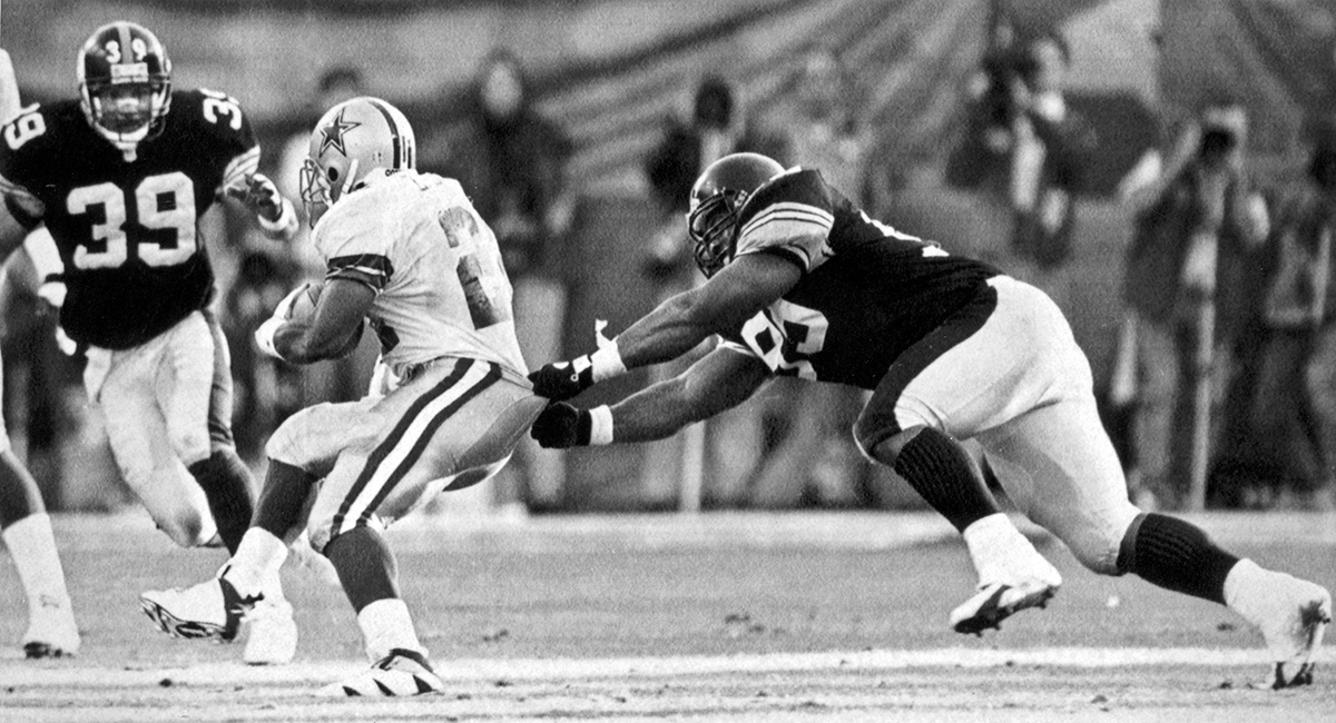 Levon Kirkland grabs Cowboys running back Emmitt Smith's pants to make a tackle in Super Bowl XXX. Smith had 18 carries for 49 yards and two touchdowns in the game. (Bob Donaldson/Post-Gazette)