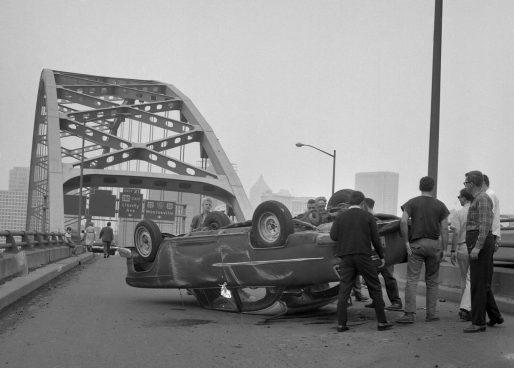 Motorists gather around the overturned Chevrolet. (Morris Berman/Post-Gazette)