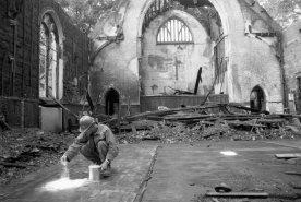 Chemist William Kinard spreads absorbent salt that detects traces of gasoline or kerosene on the church floor. (Steve Mellon/The Pittsburgh Press)