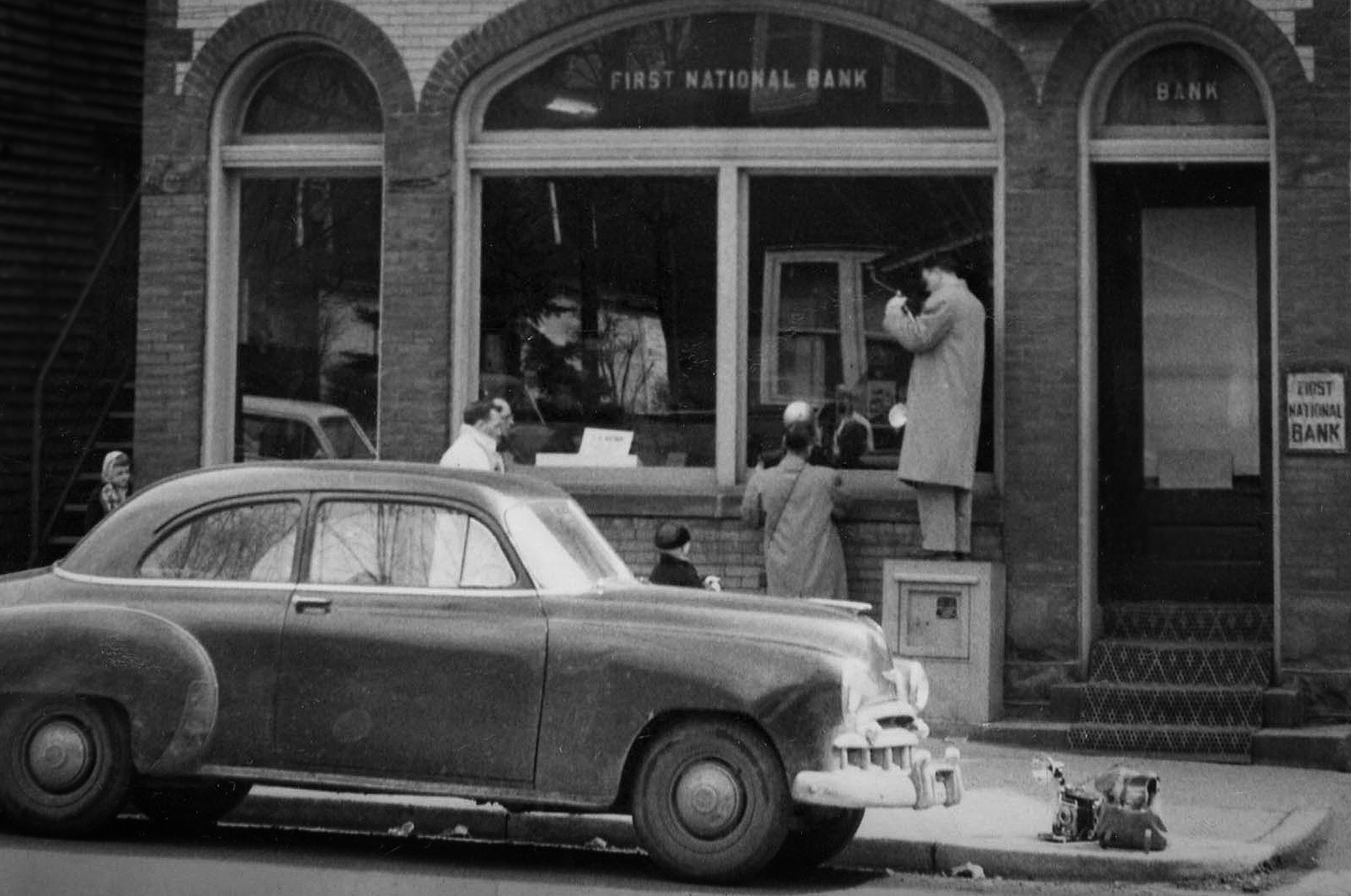 Detail of previous image, showing newspaper photographers and a young girl peering at the scene. (The Pittsburgh Press)