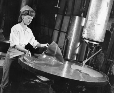 "The Clark Bar's core includes peanut butter and caramel mixed into a thick taffy. After the taffy was cooked, but before the other ingredients were added, it was poured on a giant griddle to cool. The original caption says it resembles a ""golden omelet."" Once it became lukewarm, the taffy was ready for pulling. This worker scrapes off a batch as another begins to pour out. Picture taken March 21, 1948. (Pittsburgh Press)"