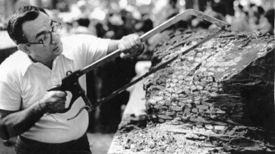 "Tony Murgid saws apart the ""Largest Candy Bar in the World,"" which was about 15 ft. long and 20 in. thick. Pieces were handed out for Kennywood visitors to enjoy. Picture taken Aug. 14, 1981. (Pittsburgh Press)"
