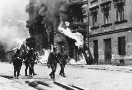 Nazi officers walk through the Warsaw Ghetto as it burns out of control in spring 1943. (Associated Press)