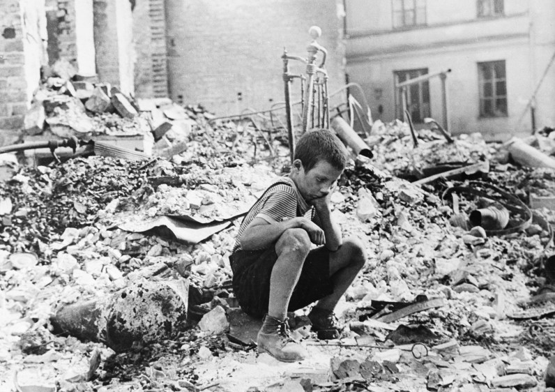 This is 1939 file photo shows a young Polish boy returning to the ruins of his home after German air raids on Warsaw, Poland. (Associated Press)