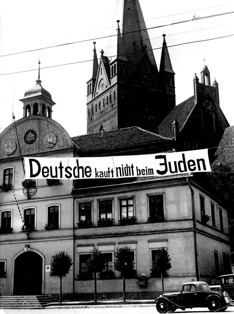 "Hundreds of posters asking Germans to boycott Jewish shops hung throughout Germany, like this one on a street in Greifenberg, Pomerania on Aug. 8, 1935. This sign reads, ""Germans don't buy in Jewish shops."" (Associated Press)"