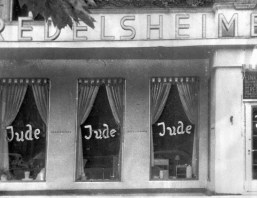 """In this June 19, 1938 file picture, the word """"Jude"""" (German for """"Jew"""") is smeared on the windows of a shop in Berlin. (Associated Press)"""