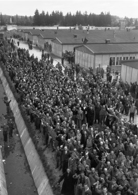 Prisoners crowd the edge of the moat and wire fencing encompassing the concentration camp at Dachau, Germany, May 3, 1945, as they shout greetings to their liberators, the 42nd Rainbow Division of the U.S. Army.