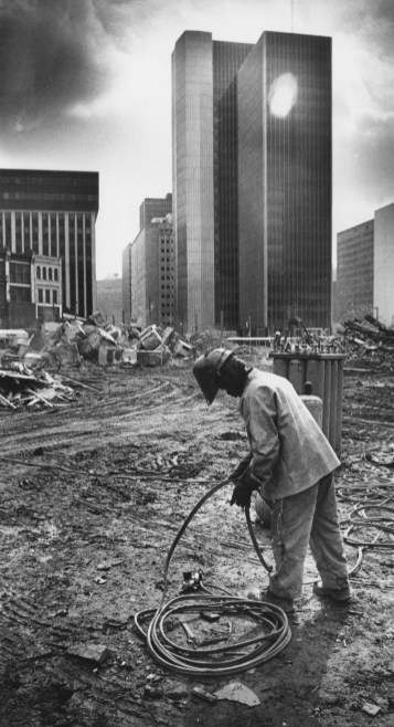 Leandrew Williams of West Mifflin rolls up a burning hose, used for cutting steel, on the site of the former Jenkins Arcade on March 23, 1984. (Tony Tye/Post-Gazette)
