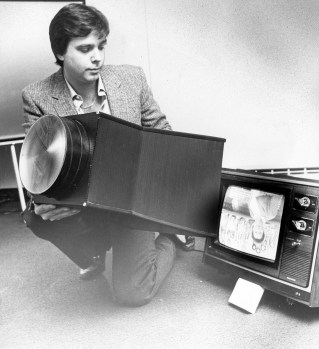 """Jim Thomason attaches a device which enlarges the image on a TV set, Feb. 3, 1982. Large screen TVs were prohibitely expensive for the average consumer at the time, but Thomason promoted his invention as being """"twice as bright and half the price."""" (Anthony Kaminski/Pittsburgh Press)"""