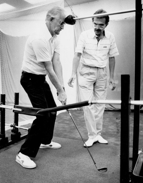 Mike Vuik, right, teaches Thom Eaton of Trafford how to use the Swing Machine to help his golf swing, June 21, 1990. (Dave Yoder/Pittsburgh Press)
