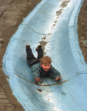 Ryry Talvitie, 4, of Finland, who currently lives in Squirrel Hill, slides hands first on a concrete slide in Frick Park, April 27, 1997. (Darrell Sapp/Post-Gazette)