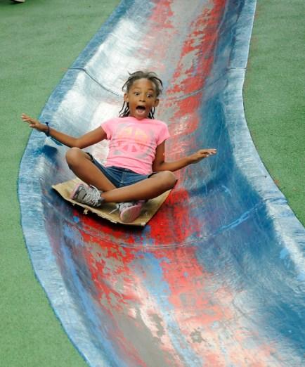 Ailani Mitchell, 7, of Homewood goes headfirst down the blue slide, Aug. 10, 2012. (Chris Kasprak/Post-Gazette)