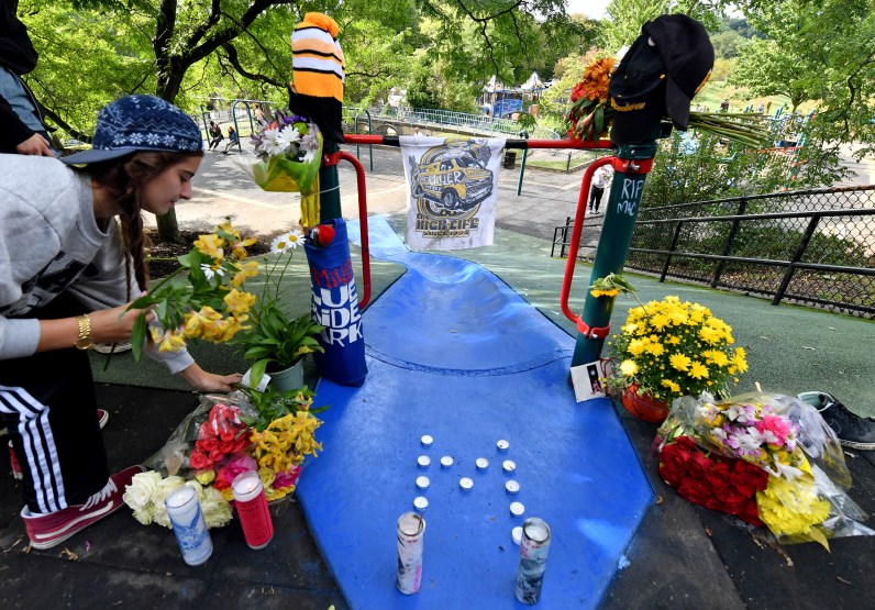 Ava Gerami, 19, of Cleveland places flowers in honor of rapper Mac Miller during a vigil, Tuesday, Sept. 11, 2018, at Blue Slide Park. (Matt Freed/Post-Gazette)