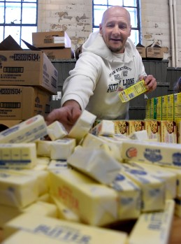 Daniel Smaglo, of Baldwin Township, takes sticks of butter out of their one pound boxes for the 1,060 baskets with food for Thanksgiving dinners on the North Side in 2017. (Darrell Sapp/Post-Gazette)