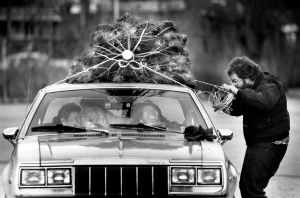 Joe Stewart ties down a tree for customers in his McKeesport Christmas tree lot, Dec. 20, 1990. (Andy Starnes/Pittsburgh Press)
