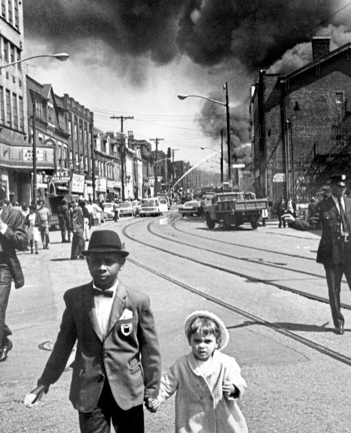 Children walk through the Hill District on Palm Sunday, April 7, 1968, as smoke from the Mainway Super Market fire billows behind them during unrest and violence following the murder of civil rights leader the Rev. Martin Luther King Jr. (Harry Coughanour/Post-Gazette)