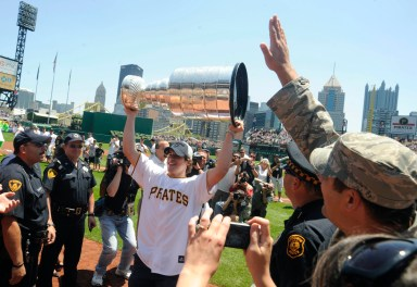 Sidney Crosby hoists the Stanley Cup as members of the Stanley Cup champion Pittsburgh Penguins attend a game between the Pittsburgh Pirates and the Detroit Tigers, Sunday, June 14, 2009, at PNC Park. (Michael Henninger / Post-Gazette)