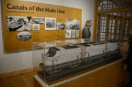 """A model of the """"Lou Ann"""" sits on the rail cars in a display case at the Portage Museum. (Darrell Sapp/Post-Gazette)"""